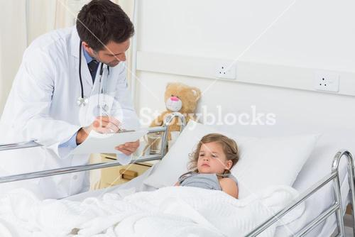 Doctor with clipboard attending ill girl