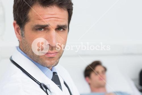 Doctor in hospital with patient in backgorund