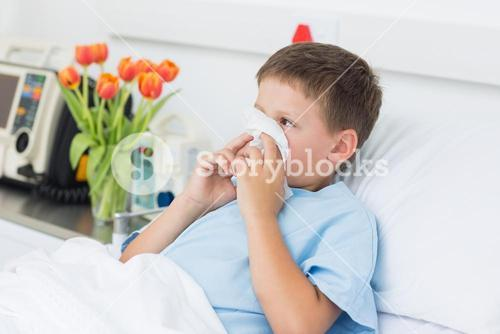 Boy blowing nose into tissue in hospital