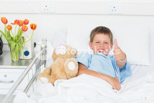 Boy gesturing thumbs up with teddy bear in hospital