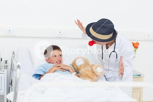 Doctor entertaining sick boy in hospital bed