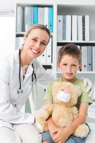 Friendly doctor with boy holding teddy bear
