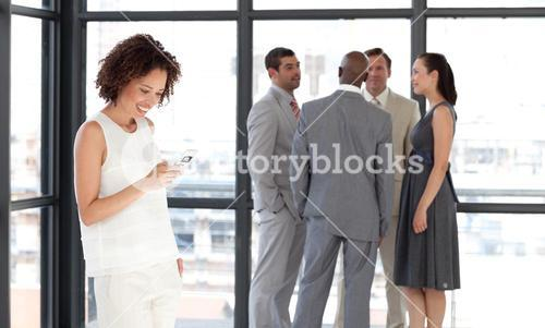 Charismatic businesswoman on phone in office with her team