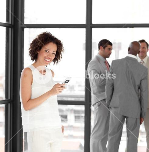 Cute businesswoman on phone in office with her team