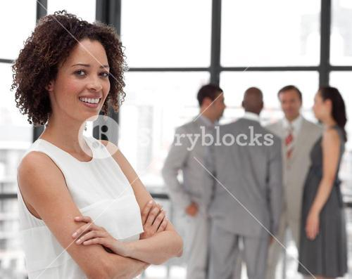 Serious businesswoman on phone in office with her team