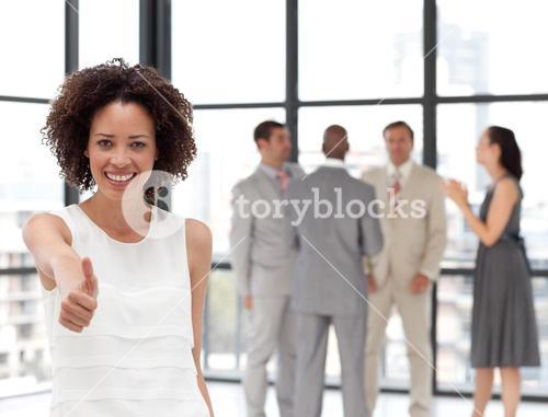 A businesswoman on phone in office with her team