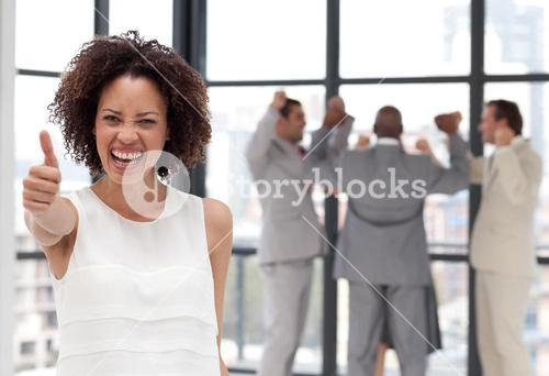 Attractive businesswoman on phone in office with her team