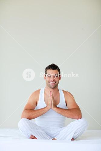 Young man doing yoga in his bedroom