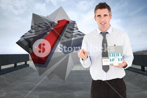 Composite image of businessman holding a key and a miniature house