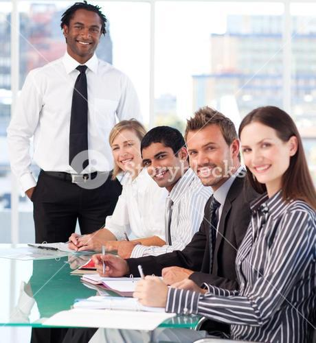 Happy business leader with his team in a meeting