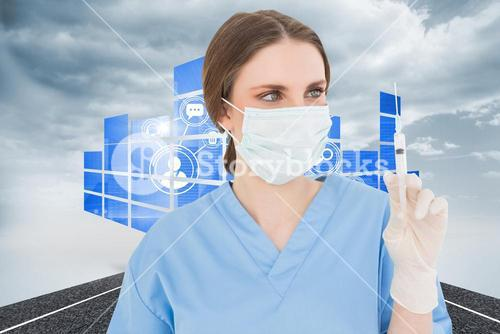 Composite image of pretty brunette female doctor holding a syringe and looking at it