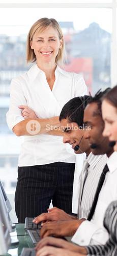 Bright female leader with a team on a call center