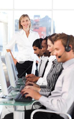 Cheerful female leader with a team on a call center