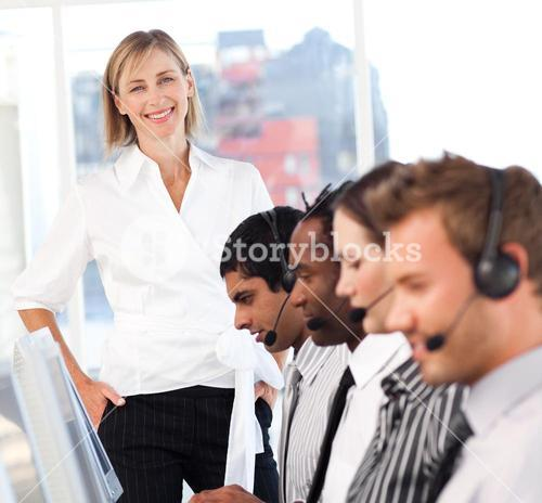Beautiful female leader with a team on a call center