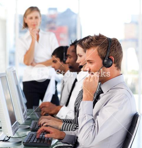 Pretty female leader with a team on a call center