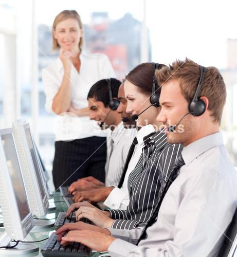 Serious female leader with a team on a call center