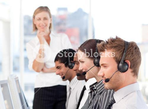 Concentrated female leader with a team on a call center
