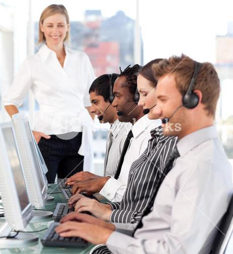 Happy female leader with a team on a call center