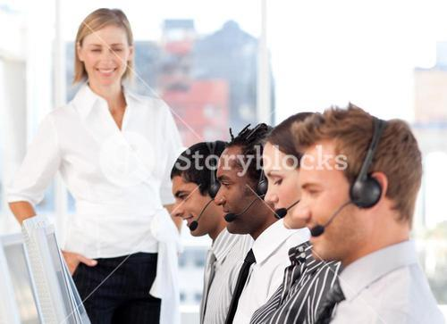 Happy female leader with her team on a call center