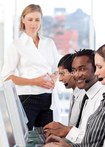 Serious female leader with her team on a call center