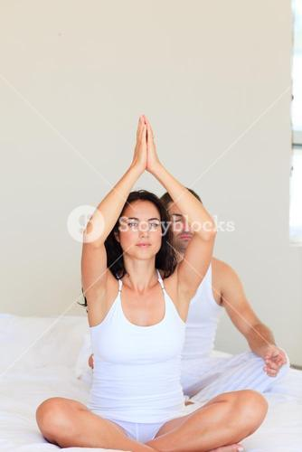 Couple practicing yoga in bed