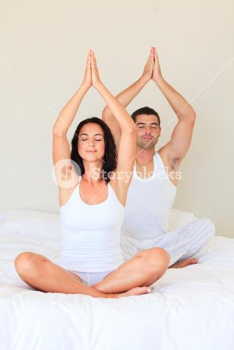 Couple sitting on bed practicing yoga