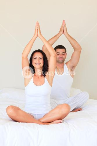 Couple sitting on bed in meditation pose