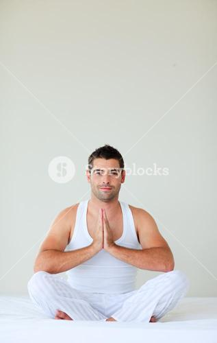 Man sitting on bed meditating with copyspace
