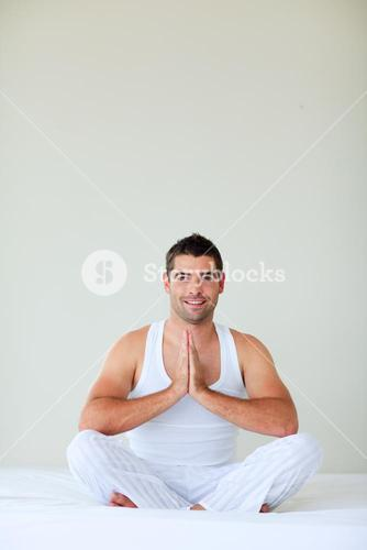 Young man meditating in bed with copyspace