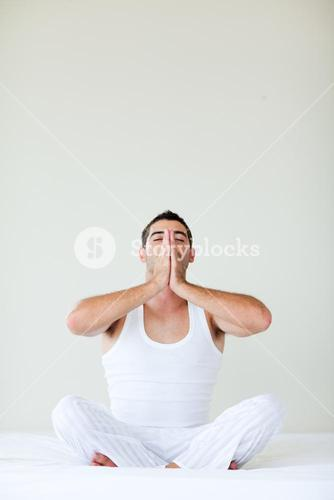 Young man doing yoga sitting in bed