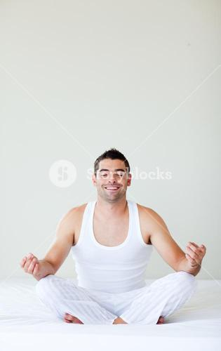 Smiling young man doing yoga in bed