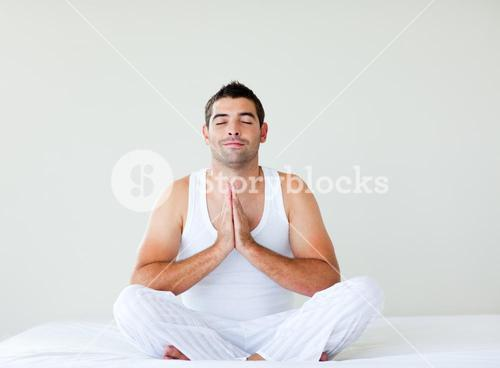 Young man practicing yoga in bed