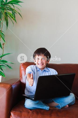 Kid using his laptop with thumb up