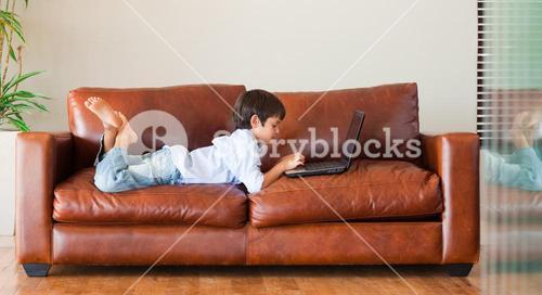 Kid playing with a laptop on the sofa