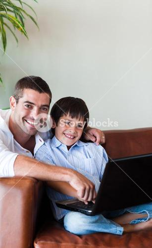 Father and son together with a computer