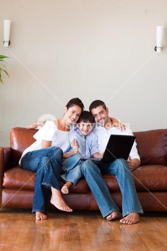 Parents and kid using a laptop with thumbs up and copyspace