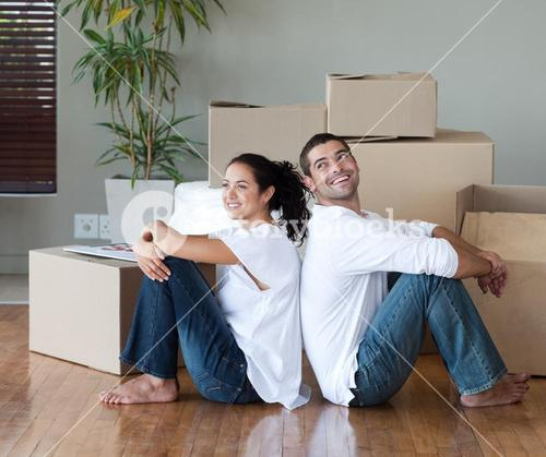 Joyful couple with unpacking boxes moving to a new house