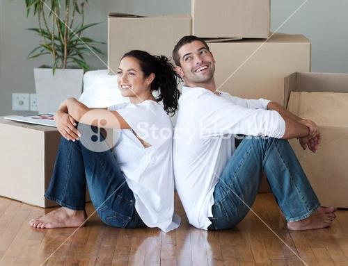Radiant couple with unpacking boxes moving to a new house