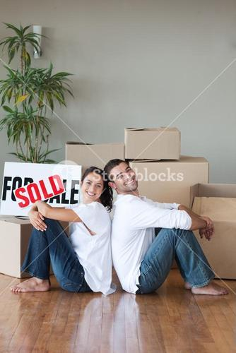 Cheerful couple with unpacking boxes moving to a new house