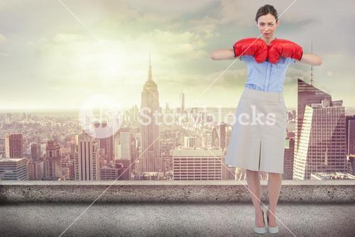 Composite image of tough businesswoman posing with red boxing gloves