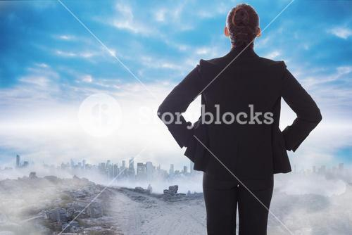Composite image of businesswoman with hands on hips