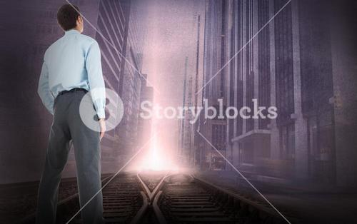 Composite image of businessman standing with hand in pockets