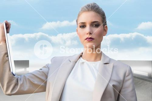Composite image of serious classy businesswoman holding tablet