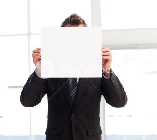 Businessman holding a white card in front of his face