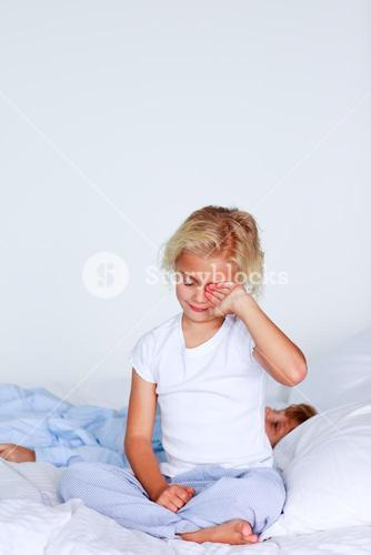 Portrait of a girl waking up in a bedroom