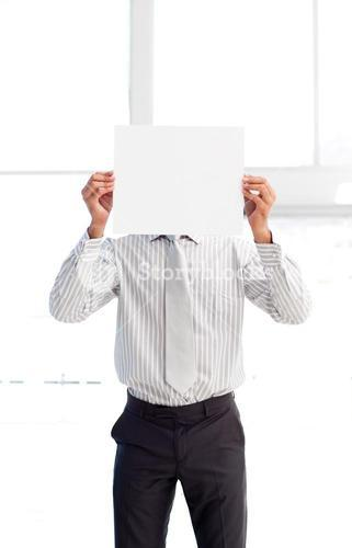 Businessman presenting a white card in front of his face