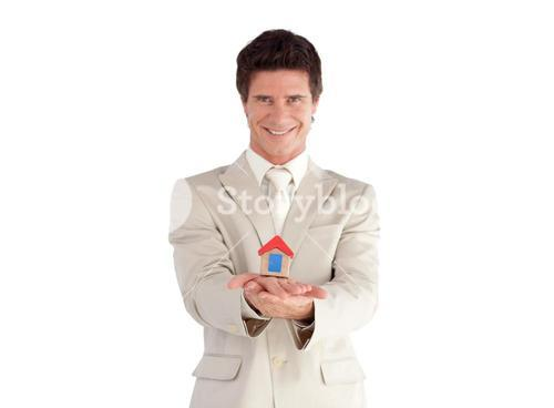 Selfassured businessman holding a house
