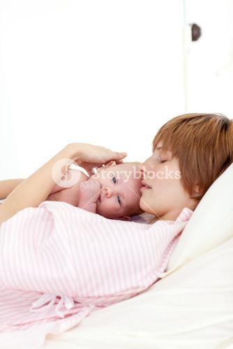 Patient relaxing with her newborn baby in bed