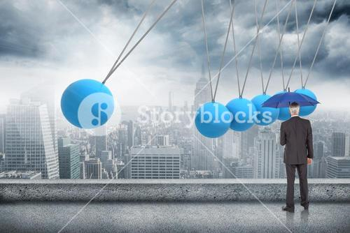 Composite image of businessman holding umbrella