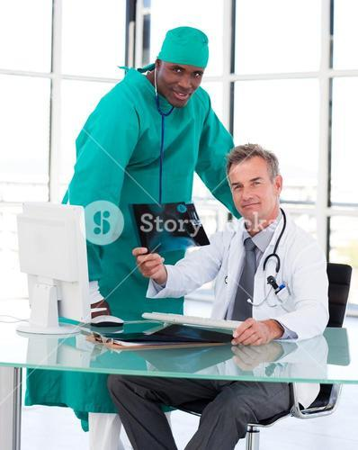 Doctors looking at the camera with an Xray